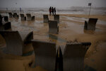 People look at the Mediterranean sea during a storm in Barcelona, Spain, Tuesday, Jan. 21, 2020. A winter storm lashed much of Spain for a third day Tuesday, leaving 200,000 people without electricity, schools closed and roads blocked by snow as it killed four people. Massive waves and gale-force winds smashed into seafront towns, damaging many shops and restaurants. (AP Photo/Emilio Morenatti)