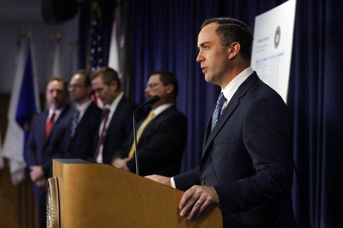 First Assistant U.S. Attorney Peter Mazza, right, speaks during a news conference Friday, Nov. 22, 2019, in San Diego. Federal agents have arrested former San Diego County Sheriff's Captain Marco Garmo under charges of operating an illegal firearms trafficking business. (AP Photo/Gregory Bull)