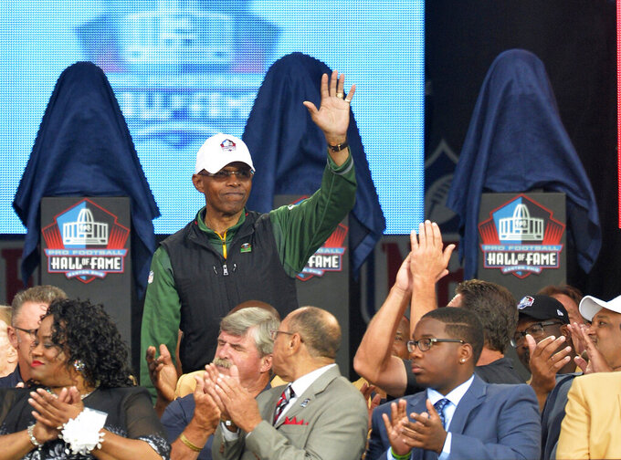 FILE - In this Aug. 2, 2014, file photo,  Gale Sayers is introduced during the Pro Football Hall of Fame enshrinement ceremony in Canton, Ohio. Six Hall of Famers and 230 past and present players and coaches were on hand as the Bears kicked off their 100th anniversary celebration weekend on Friday, June 7, 2019. And when Sayers was wheeled onto the stage, the roar from the crowd could have drowned out the jets nearby at O'Hare International Airport. Weakened by dementia diagnosed five years ago, Sayers still made the 130-mile trip from his home in Wakarusa, Ind. (AP Photo/David Richard, File)