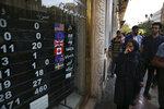 FILE - In this Oct. 2, 2018 file photo, an exchange shop displays rates for various currencies, in downtown Tehran, Iran. Iran is bracing for the restoration of U.S. sanctions on its vital oil industry set to take effect on Monday, Nov. 5, 2018, as it grapples with an economic crisis that has sparked sporadic protests over rising prices, corruption and unemployment. The oil sanctions will target the country's largest source of revenue in the most punishing action taken since the Trump administration withdrew from the 2015 nuclear agreement in May. (AP Photo/Vahid Salemi, File)