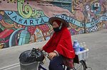 A traditional herbal drink vendor wearing a mask to help curb the spread of the coronavirus outbreak cycles past a mural with writings that read