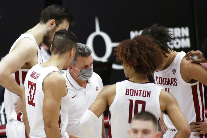 Washington State coach Kyle Smith, center, talks to the team during a break in play in the second half of an NCAA college basketball game against Utah in Pullman, Wash., Thursday, Jan. 21, 2021. (AP Photo/Young Kwak)