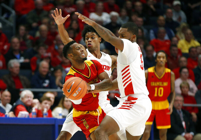 Grambling State guard Trevell Cunningham, left, is pressured by Dayton guards Trey Landers, right, and Jhery Matos, rear, during the first half of an NCAA college basketball game, Monday Dec. 23, 2019, in Dayton, Ohio. (AP Photo/Gary Landers)