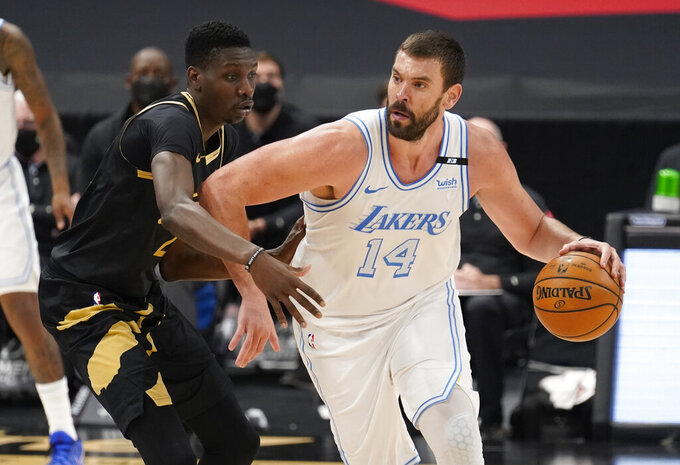 FILE - In this April 6, 2021, file photo, Los Angeles Lakers center Marc Gasol (14) drives as Toronto Raptors forward Chris Boucher (25) defends during an NBA basketball game in Tampa, Fla. The Lakers have traded the rights to Gasol back to the Memphis Grizzlies, where the 36-year-old center spent his first 11 NBA seasons. The Lakers also sent a second-round pick in 2024 and cash to Memphis on Friday, Sept. 10, in exchange for the draft rights to Chinese big man Wang Zhelin. (AP Photo/Chris O'Meara, File)