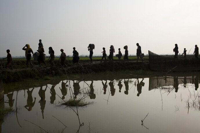 -FILE- In this Tuesday, Sept. 5, 2017, file photo members of Myanmar's Rohingya ethnic minority walk through rice fields after crossing the border into Bangladesh near Cox's Bazar's Teknaf area. Gambia has filed a case at the United Nations' highest court in The Hague, Netherlands, Monday, Nov. 11, 2019, accusing Myanmar of genocide in its campaign against the Rohingya Muslim minority. A statement released Monday by lawyers for Gambia says the case also asks the International Court of Justice to order measures