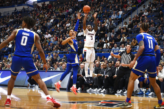 Connecticut's Alterique Gilbert, center, shoots over Tulsa's Isaiah Hill in the first half of an NCAA college basketball game, Sunday, Jan. 26, 2020, in Hartford, Conn. (AP Photo/Jessica Hill)