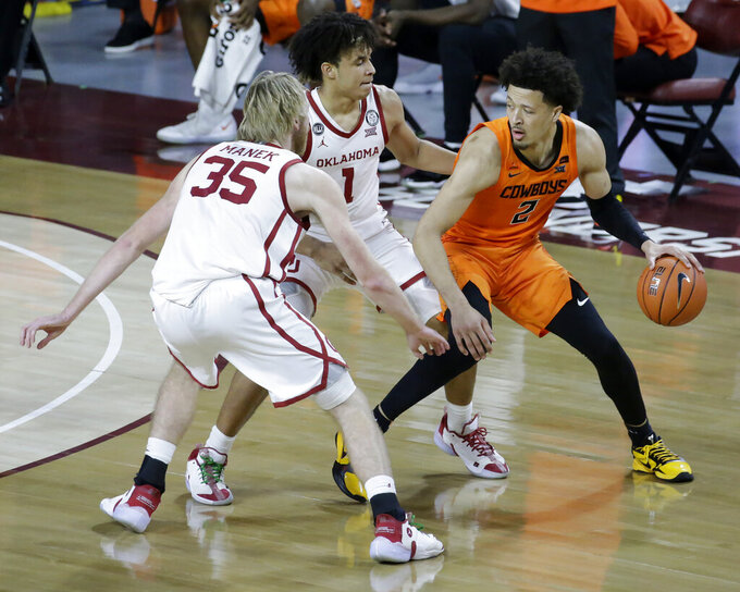 Oklahoma State guard Cade Cunningham (2) goes against Oklahoma forward Brady Manek (35) and forward Jalen Hill (1) during the second half of an NCAA college basketball game, Saturday, Feb. 27, 2021, in Norman, Okla. (AP Photo/Garett Fisbeck)