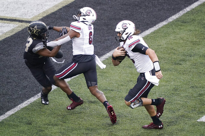 South Carolina quarterback Collin Hill (15) follows the blocking of wide receiver Josh Vann (6) as Hill gets past Vanderbilt cornerback Jaylen Mahoney (23) for a touchdown in the second half of an NCAA college football game Saturday, Oct. 10, 2020, in Nashville, Tenn. South Carolina won 41-7. (AP Photo/Mark Humphrey)