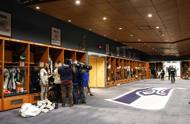 The media surrounds Seattle Seahawks' player Jacob Hollister for an interview as players clean out their lockers at Seahawks headquarters in Renton, Wash. Monday, Jan. 13, 2020. (Ellen M. Banner/The Seattle Times via AP)
