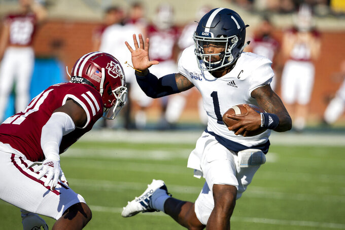 Georgia Southern quarterback Shai Werts (1) runs for yardage against Massachusetts defensive back Te'Rai Powell (21) during the first half of an NCAA football game, Saturday, Oct. 17, 2020, in Statesboro, Ga. (AP Photo/Stephen B. Morton)