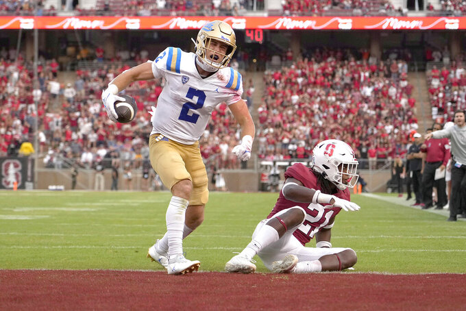 UCLA wide receiver Kyle Philips (2) celebrates after catching a pass for a touchdown in front of Stanford safety Kendall Williamson (21) during the second half of an NCAA college football game Saturday, Sept. 25, 2021, in Stanford, Calif. UCLA won 35-24. (AP Photo/Tony Avelar)