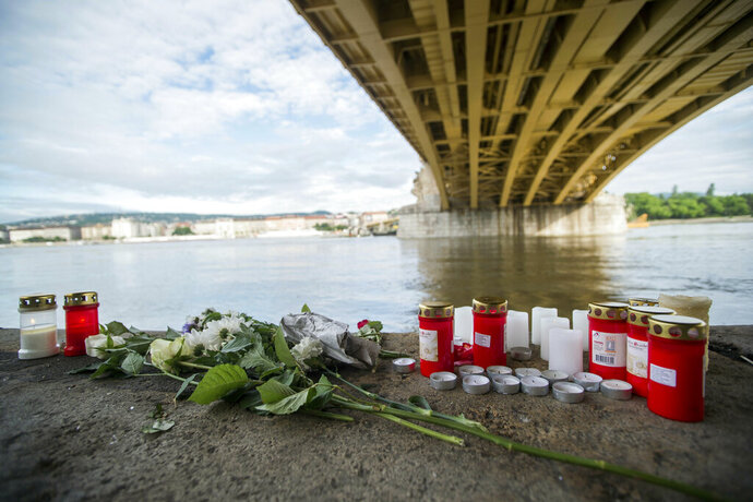 FILE - In this Friday, May 31, 2019 file photo, candles and flowers are left under the Margaret Bridge near the spot where a boat carrying South Korean tourists sank in Budapest, Hungary. The Ukrainian captain of a cruise ship involved in a crash on the Danube River that killed 28 people is back in police custody. Hungarian police said Monday, July 29, 2019 that the captain, who was out on bail after being detained for his suspected responsibility in the May 29 collision, is now also suspected of failing to provide assistance after the accident and was being interrogated. Only seven South Korean tourists survived the collision which capsized and sank their tour boat. (Zoltan Balogh/MTI via AP, File)