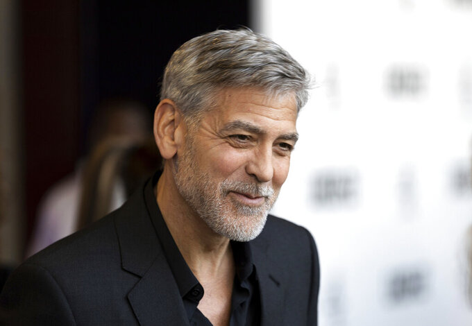 """FILE - In this Wednesday, May 15, 2019, file photo, actor George Clooney talks to reporters on arrival at the premiere of the television mini-series """"Catch22,"""" in London. Clooney was honored Monday, Dec. 7, 2020, by co-stars and colleagues at the annual film benefit for the Museum of Modern Art, held virtually. (Photo by Grant Pollard/Invision/AP, File)"""