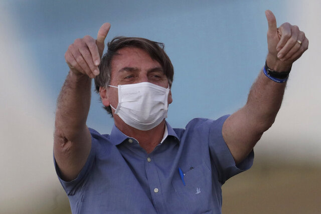 FILE - In this  July 17, 2020, file photo, Brazil's President Jair Bolsonaro who is infected with COVID-19, wears a protective face mask as he flashes thumbs-up at supporters during a Brazilian flag retreat ceremony outside his official residence Alvorada Palace, in Brasilia, Brazil. Bolsonaro announced his illness in July and used it to publicly extol hydroxychloroquine, the unproven malaria drug that he'd been promoting as a treatment for COVID-19 and was taking himself. (AP Photo/Eraldo Peres, File)