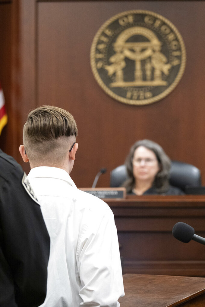 Robert Aaron Long stands before Judge Ellen McElyea in Superior Court of Cherokee County in Canton, Ga. on Tuesday, July 27, 2021. The man accused of killing eight people, most of them women of Asian descent, at Atlanta-area massage businesses pleaded guilty to four of the murders. He was handed four sentences of life without parole. Robert Aaron Long still faces the death penalty in the four other deaths, which are being prosecuted in a different county. (Ben Gray/Atlanta Journal-Constitution via AP, Pool)