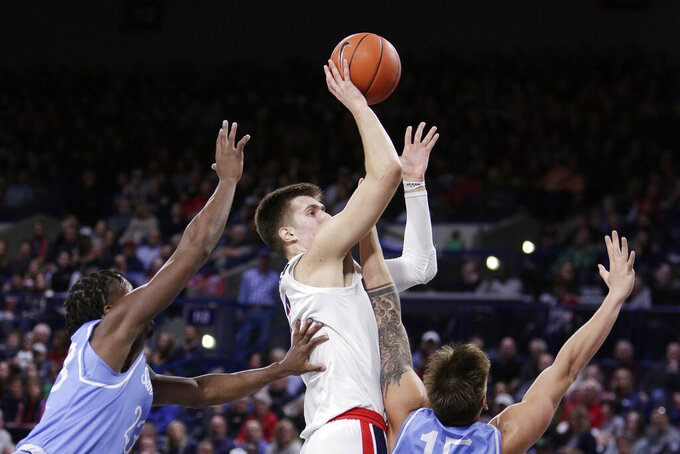 Gonzaga forward Filip Petrusev, center, shoots between San Diego forward James Jean-Marie, left, and forward Alex Floresca during the first half of an NCAA college basketball game in Spokane, Wash., Thursday, Feb. 27, 2020. (AP Photo/Young Kwak)