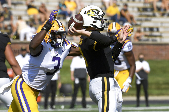Missouri quarterback Connor Bazelak, right, throws under pressure from LSU offensive lineman Andre Anthony (3) during the first half of an NCAA college football game Saturday, Oct. 10, 2020, in Columbia, Mo. (AP Photo/L.G. Patterson)