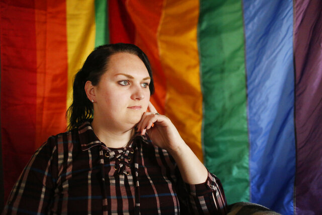 FILE - In this Feb. 6, 2018, file photo, Destiny Clark, 33, of Odenville, Ala., sits infant of a pride flag for a portrait in Odenville, Ala. Alabama's policy requiring a transgender person to undergo full gender reassignment surgery before they can change the sex on their driver's license is unconstitutional, a federal judge ruled Friday, Jan. 15, 2021. (AP Photo/Brynn Anderson, File)