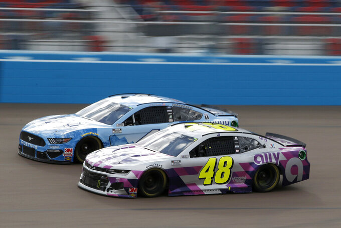 Jimmie Johnson (48) and Kevin Harvick (4) race side by side through Turn 4 during the NASCAR Cup Series auto race at Phoenix Raceway, Sunday, Nov. 8, 2020, in Avondale, Ariz. (AP Photo/Ralph Freso)
