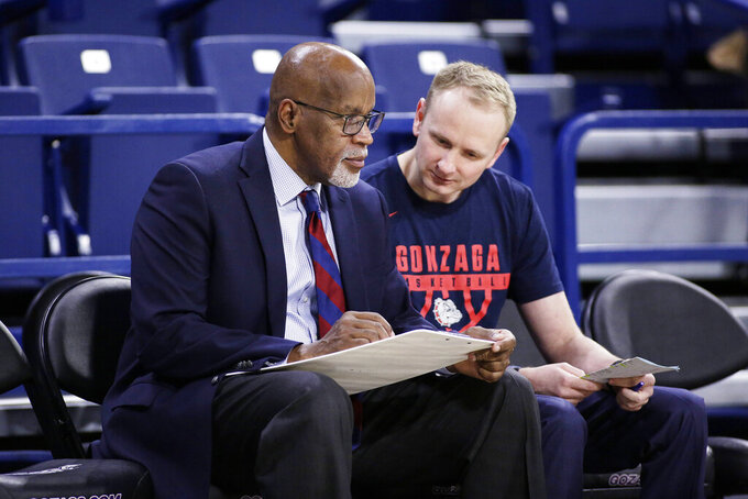 FILE - Gonzaga assistant coach Donny Daniels, left, and director of basketball operations Stephen Gentry speak before an NCAA college basketball game against Texas-Arlington in Spokane, Wash., in this Tuesday, Dec. 18, 2018, file photo. Former Gonzaga player and former Gonzaga director of operations Stephen Gentry was hired Monday, May 24, 2021, as an assistant basketball coach to replace Tommy Lloyd, who left the Bulldogs to become the head coach at Arizona. Gentry was most recently an assistant coach at Illinois. (AP Photo/Young Kwak, File)
