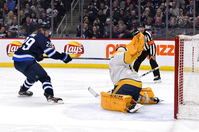 Nashville Predators goaltender Juuse Saros (74) makes a save on a penalty shot Winnipeg Jets' Patrik Laine (29) during the second period of an NHL hockey game Tuesday, Feb. 4, 2020, in Winnipeg, Manitoba. (Fred Greenslade/The Canadian Press via AP)