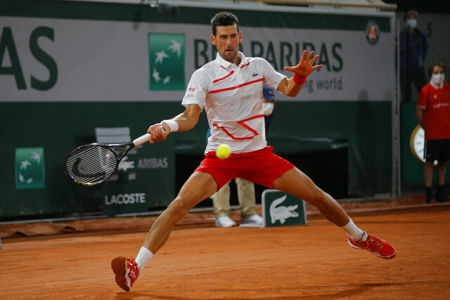 Serbia's Novak Djokovic plays a shot against Sweden's Mikael Ymer in the first round match of the French Open tennis tournament at the Roland Garros stadium in Paris, France, Tuesday, Sept. 29, 2020. (AP Photo/Michel Euler)