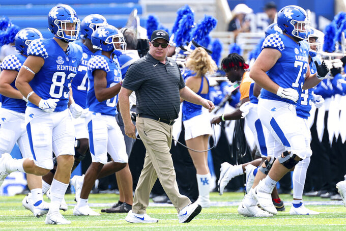 Kentucky head coach Mark Stoops walks onto the field with his team before a NCAA college football game against Chattanooga in Lexington, Ky., Saturday, Sept. 18, 2021. (AP Photo/Michael Clubb)