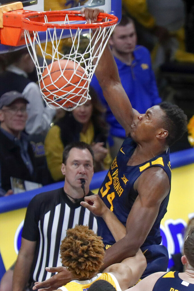 Oscar Tshiebwe (34) dunks over Pittsburgh's Terrell Brown during the second half of an NCAA college basketball game, Friday, Nov. 15, 2019, in Pittsburgh. (AP Photo/Keith Srakocic)