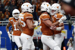 Texas quarterback Sam Ehlinger (11) celebrates his touchdown run against Utah with teammates during the second half of the Alamo Bowl NCAA college football game in San Antonio, Tuesday, Dec. 31, 2019. (AP Photo/Eric Gay)