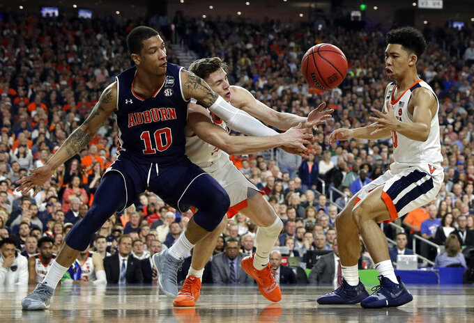Auburn's Samir Doughty (10) battles for a loose ball against Virginia's Kyle Guy and Kihei Clark (0) during the first half in the semifinals of the Final Four NCAA college basketball tournament, Saturday, April 6, 2019, in Minneapolis. (AP Photo/David J. Phillip)