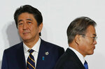 FILE - In this June 28, 2019, file photo, South Korean President Moon Jae-in, right, walks by Japanese Prime Minister Shinzo Abe upon his arrival for a welcome and family photo session at the G-20 leaders summit in Osaka, western Japan. Japan and South Korea, two major U.S. allies, are again at odds, this time over Tokyo's decision to tighten controls on exports of sensitive materials that are mainly used in computer chips and display screens used in TVs and smartphones. The tensions reflect animosities that have persisted for decades. (Kim Kyung-Hoon/Pool Photo via AP, File)