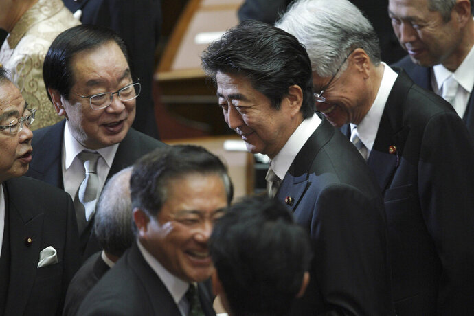 Japanese Prime Minister Shinzo Abe, center, chats with lawmakers after the opening of an extraordinary session at the upper house of parliament in Tokyo Friday, Oct. 4, 2019. (AP Photo/Eugene Hoshiko)