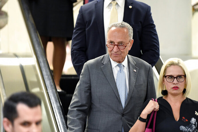 FILE - In this July 10, 2019, file photo, Senate Minority Leader Sen. Chuck Schumer of N.Y., rides the escalator on Capitol Hill in Washington, as he heads to a briefing on election security. While House Democrats are haggling over whether to consider impeachment of President Donald Trump, Senate Democrats are focusing on a different angle of former special counsel Robert Mueller's report _ securing future elections from foreign interference. (AP Photo/Susan Walsh, File)