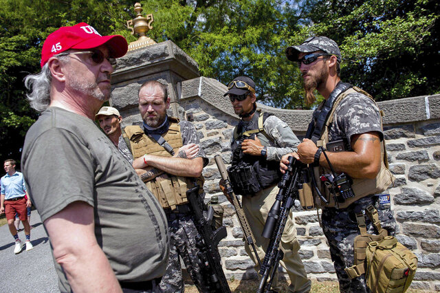 A group of individuals, some armed, talk near an entrance to the Gettysburg National Cemetery in Gettysburg National Military Park on Saturday, July 4, 2020 in Gettysburg, Pa. Since their birth in the mid-1990s, groups calling themselves constitutional militia have primarily stayed hidden, but this year, they're out — fully armed — to patrol demonstrations or rally at the state capital demanding reopening of businesses during the pandemic.  (Dan Rainville/York Daily Record via AP)