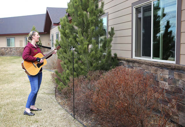 In this April 17, 2020, photo, Kirsten Wells plays guitar for residents of Rising Mountains Assisted Living in Bigfork, Mont. She played songs like