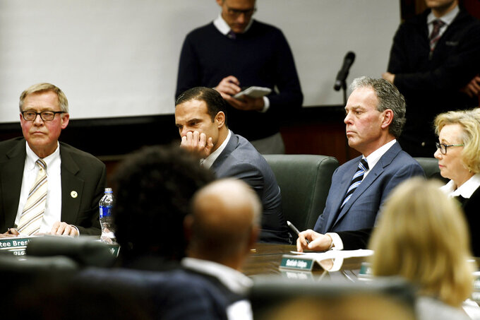 From left, Board Chairman Brian Breslin, Trustees Brian Mosallam, Dan Kelly and Melanie Foster look on during a Michigan State University Board of Trustees meeting on Friday, Jan. 26, 2018, in the board room at the Hannah Administration Building on the MSU campus in East Lansing, Mich. Michigan State University's athletic director announced his retirement Friday, becoming the second university official to step down this week over the school's handling of sexual abuse allegations against disgraced former sports doctor Larry Nassar. (Nick King /Lansing State Journal via AP)