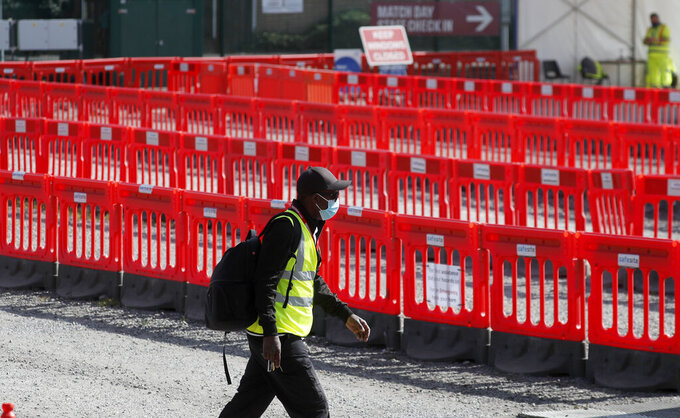 A staff member walks past empty lanes of a Covid-19 drive thru testing facility at Twickenham stadium in London, Thursday, Sept. 17, 2020. Britain has imposed tougher restrictions on people and businesses in parts of northeastern England on Thursday as the nation attempts to stem the spread of COVID-19, although some testing facilities remain under-utilised. (AP Photo/Frank Augstein)