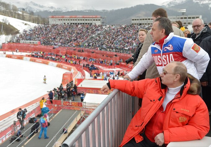 FILE - In this file photo taken Saturday, March 8, 2014, Russian President Vladimir Putin, foreground, and Russia's sports minister Vitaly Mutko, standing behind, watch downhill ski competition of the 2014 Winter Paralympics in Roza Khutor mountain district of Sochi, Russia.  Russia's status as an Olympic team and reputation as a serial cheater in international sports goes on trial on Monday Nov. 2, 2020, as the Court of Arbitration for Sport will start hearings about a manipulated database from the Moscow testing laboratory.  (Alexei Nikolsky, Sputnik, Kremlin Pool Photo via AP, File)