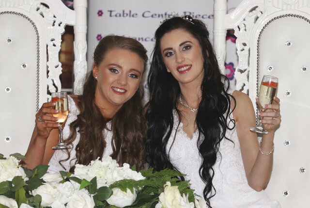 Robyn Peoples, left, 26, and Sharni Edwards, 27, pose together after becoming the first same sex couple to marry in Northern Ireland, in Carrickfergus, Northern Ireland, Tuesday Feb. 11, 2020. Two women tied the knot Tuesday in Northern Ireland's first same-sex wedding, after the region became the last part of the United Kingdom to legalize gay marriage. (Liam McBurney/PA via AP)