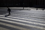 A man crosses an empty street during a nationwide confinement to counter the Covid-19, in Paris, Saturday, April 4, 2020. The new coronavirus causes mild or moderate symptoms for most people, but for some, especially older adults and people with existing health problems, it can cause more severe illness or death. (AP Photo/Christophe Ena)