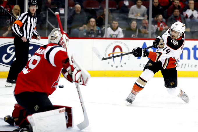 FILE - In this Dec. 18, 2019, file photo, Anaheim Ducks center Adam Henrique (14) scores a goal against New Jersey Devils goaltender Mackenzie Blackwood (29) during the first period of an NHL hockey game in Newark, N.J. Linemates Henrique and Jakob Silfverberg bucked their team's offensive struggles with a pair of impressive seasons, and they will be a foundation of the rebuilding effort. Henrique was particularly productive, leading the roster with 43 points. They are both locked into long-term contracts .(AP Photo/Kathy Willens, File)