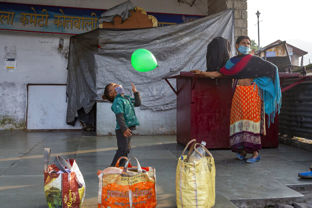 A two-and-a-half years old boy plays with a balloon as his mother waits to get work as a laborer at a town square in Dharmsala, India, Wednesday, Sept. 23, 2020. The nation of 1.3 billion people is expected to become the coronavirus pandemic's worst-hit country within weeks, surpassing the United States. (AP Photo/Ashwini Bhatia)