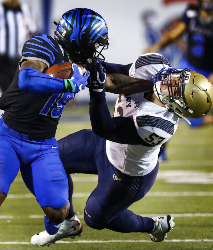 Memphis running back Kenneth Gainwell, left, stiff-arms Navy defender Tama Tuitele during an NCAA college football game Thursday, Sept. 26, 2019, in Memphis, Tenn. (Mark Weber/Daily Memphian via AP)