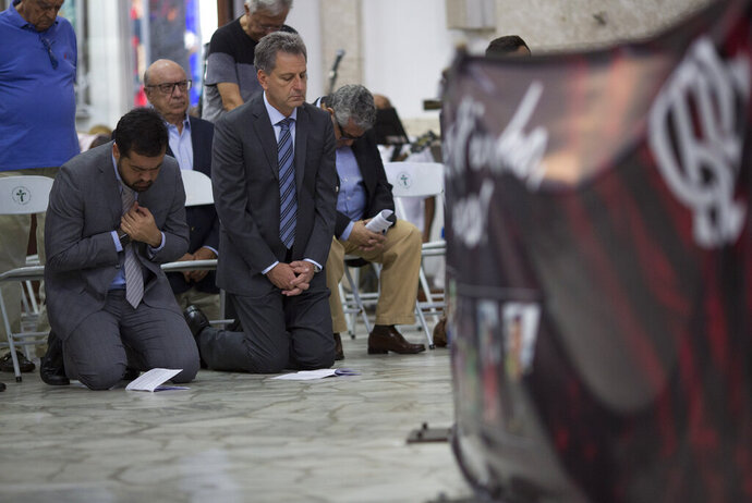 Flamengo soccer club president Rodolfo Landim, right, attends a mass in honor of the 10 teenage soccer players who were killed by a fire at the Flamengo training center last Friday, in Rio de Janeiro, Brazil, Friday, Feb. 15, 2019. The victims were between 14 and 16 years old. Police are still investigating what caused the fire. (AP Photo/Silvia Izquierdo)