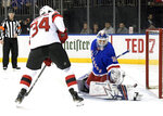 New York Rangers goaltender Henrik Lundqvist (30) deflects the puck as New Jersey Devils' Eric Tangradi looks for a rebound during the first period of an NHL hockey game Saturday, March 9, 2019, at Madison Square Garden in New York. (AP Photo/ Bill Kostroun)