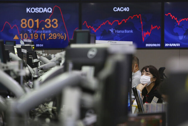 A currency trader watches monitors at the foreign exchange dealing room of the KEB Hana Bank headquarters in Seoul, South Korea, Friday, Aug. 21, 2020. Asian shares were higher Friday on hopes for development of a coronavirus vaccine, although worries remained about long-term economic damage from the pandemic. (AP Photo/Ahn Young-joon)
