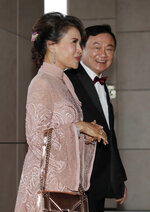 Former Thai Prime Minister Thaksin Shinawatra, right, walks with Princess Ubolratana of Thailand as they arrive the wedding of his youngest daughter Paetongtarn