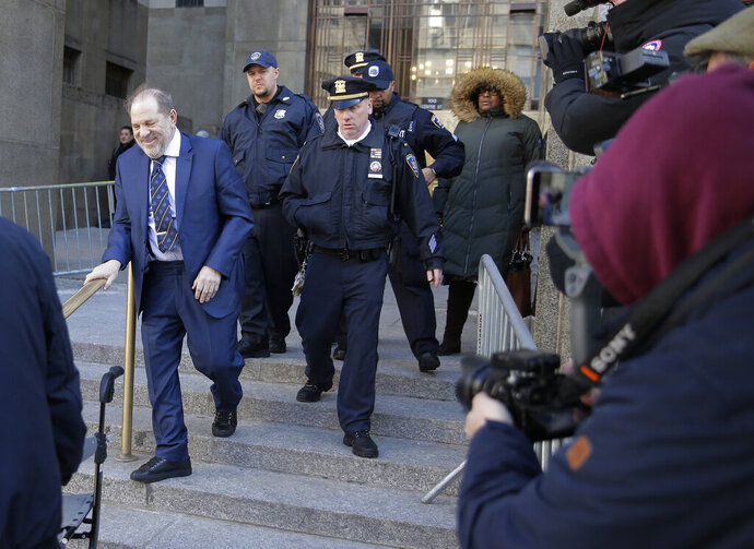 Harvey Weinstein, left, leaves a Manhattan courthouse after closing arguments in his rape trial in New York, Friday, Feb. 14, 2020. (AP Photo/Seth Wenig)