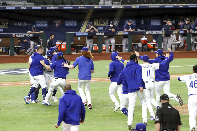 Los Angeles Dodgers players mob relief pitcher Julio Urias after the final out as they defeat the Atlanta Braves 4-3 in Game 7 of a baseball National League Championship Series, Sunday, Oct. 18, 2020, in Arlington, Texas. (Curtis Compton/Atlanta Journal-Constitution via AP)