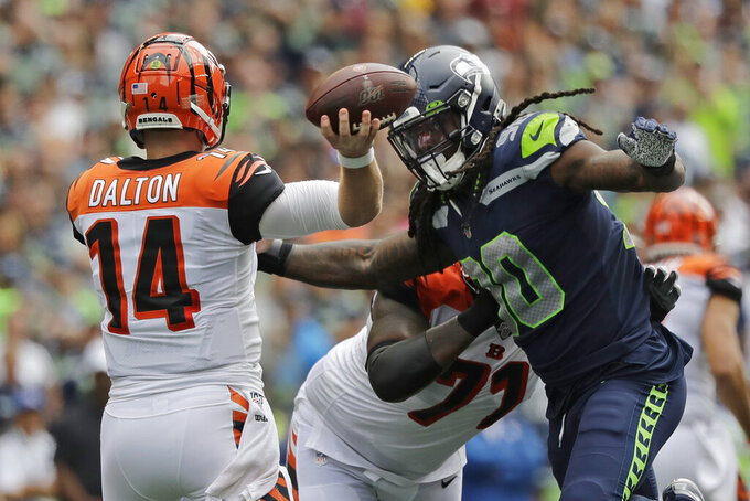 Cincinnati Bengals quarterback Andy Dalton (14) passes under pressure from Seattle Seahawks defensive end Jadeveon Clowney, right, for a touchdown to wide receiver John Ross (not shown) during the first half of an NFL football game, Sunday, Sept. 8, 2019, in Seattle. (AP Photo/John Froschauer)